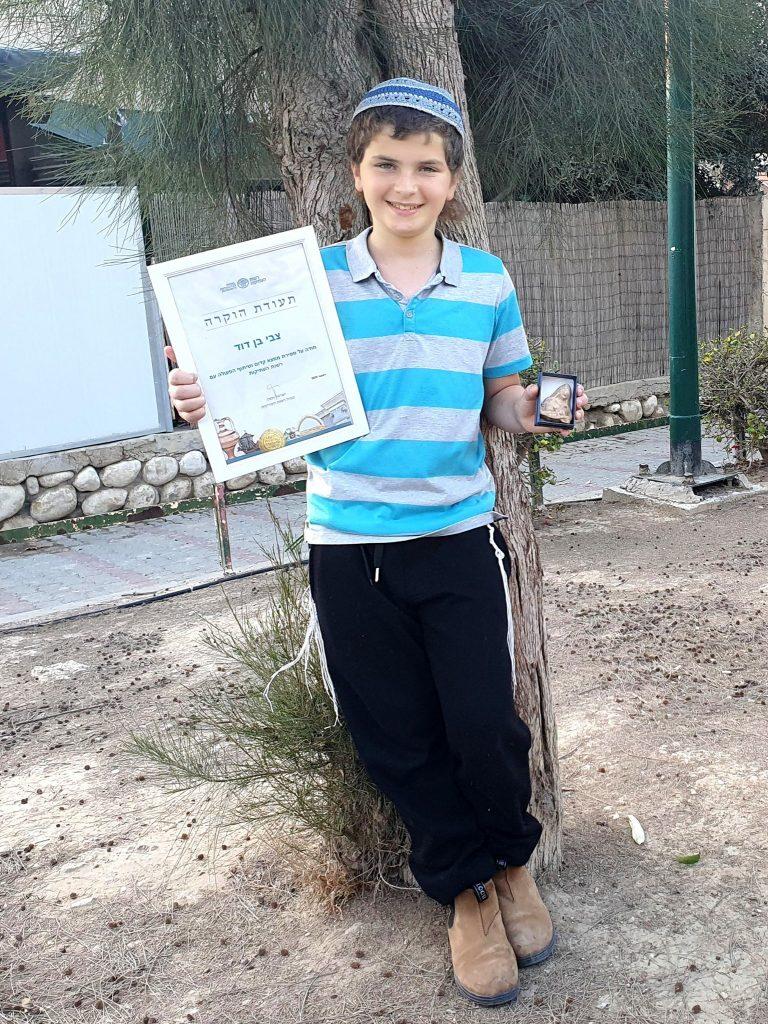 Zvi Ben-David, 11 ans, avec l'ancienne figurine.  Avec l'aimable autorisation de l'Israel Antiquities Authority.