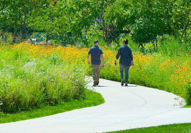 Un couple marche le long d'une partie terminée de la boucle de Louisville dans le parc de Floyd's Fork, à côté d'un champ de tournesols.  La boucle est un réseau de sentiers estimé à 100 milles qui finira par encercler la ville et relier les parcs et quartiers existants et nouveaux aux attractions civiques, aux alternatives de transport et aux possibilités de loisirs.  27 juin 2019