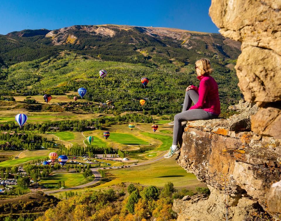 Femme assise à flanc de falaise en regardant le festival de montgolfières