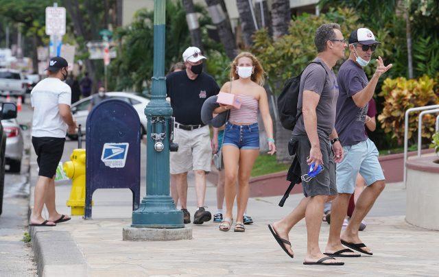 Les visiteurs masqués et démasqués se promènent le long de l'avenue Kalakaua à mesure que de nouveaux visiteurs arrivent.  Le samedi, les arrivées ont dépassé près de 25 000 personnes.  24 mars 2021